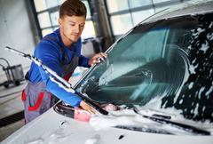 Man worker washing windshield with sponge on a car wash Stock Photos