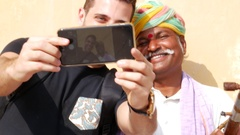 Tourist taking a selfie with a Traditional Rajasthani Musician in Jaipur, India Stock Footage