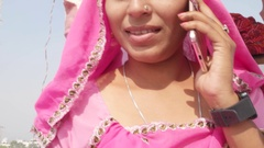 Handheld portrait of an Indian woman on cell phone mobile at Pushkar, Rajasthan Stock Footage