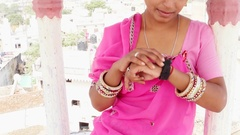 Handheld portrait of an Indian woman using her smart watch at Pushkar, Rajasthan Stock Footage
