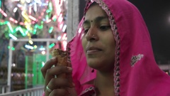 Tilt to Rajasthani woman eating ice cream at a fun fair Pushkar Mela carnival Fe Stock Footage