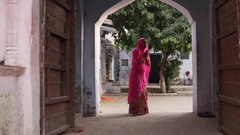 Indian woman in a pink sari with hands folded visiting a temple in Pushkar, Raja Stock Footage