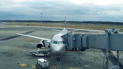 Modern silver airliner with attached jet bridge at the airport 4K steadicam Stock Footage