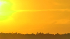 Dense clouds and the atmosphere distort a round disk setting the sun. Stock Footage