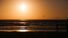 Silhouettes walking beach during sunset timelapse Stock Footage