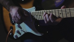 Guitarist plays hard rock by electric guitar at the dark record studio close-up Stock Footage