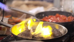The cook pan fries meat. The man fries meat on the burning frying pan. Fire on a Stock Footage