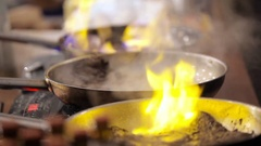 The cook pan fries meat with fire. The man fries meat on the burning frying pan Stock Footage