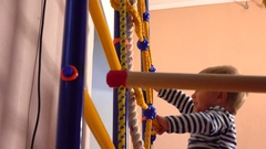 Happy little blond boy climbs up the ladder in playroom. Kid sport, success or Stock Footage
