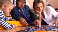 Happy caucasian family assembling puzzle together. Parents and their little boy Stock Footage