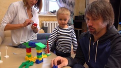 Little kid and his mom and dad playing with construction set at home together Stock Footage