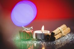 Cinnamon stick, lit candle and gift Stock Photos
