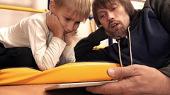 Dad and his son watching cartoons on tablet PC together. Parental control Stock Footage