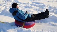 A happy child rides in snowtube on a snowy hill Stock Footage