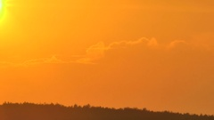 The sun during a sunset lights clouds in red color and hides for them. Stock Footage