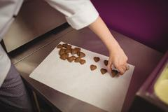 Worker arranging heart shaped chocolates on wax paper Stock Photos