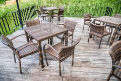The wood table on natural outdoor of a restaurant with tree and cloudy sky Kuvituskuvat