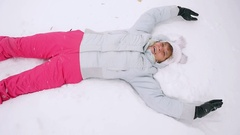 Happy mature woman lying in snowdrift enjoying snowfall in slowmotion. 1920x1080 Stock Footage