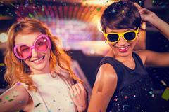 Composite image of smiling female friends dancing on dance floor Stock Photos
