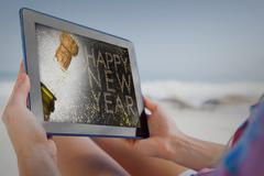 Composite image of woman sitting on beach in deck chair using tablet pc Stock Photos