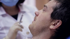 Dentist doing injection to his patient in dental clinic Stock Footage