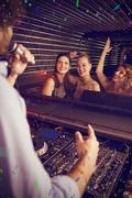 Composite image of male disc jockey playing music with three women dancing on Stock Photos