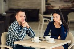 Young unhappy married couple having serious quarrel at cafe Stock Photos