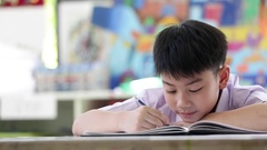 Asian child in student uniform reading and writing  . Stock Footage