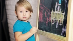 Little Boy Drawing with Chalk on Blackboard Stock Footage
