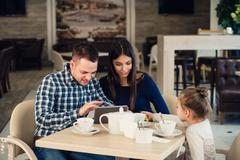 Family, parenthood, technology people concept - happy mother, father and little Stock Photos