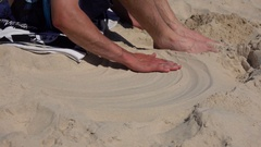 Young Man Draw a Sketch Heart Shape in Sand, Slow Motion Stock Footage