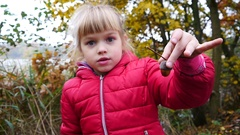 Cute little kid girl portrait during walk in nature autumn park hold an acorn Stock Footage