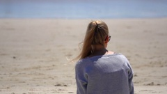 Australia, Byron Bay,Young Girl Sit on the Beach, Look at Ocean, Slow Motion Stock Footage