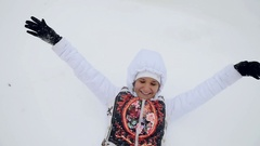 Happy young woman lying in snowdrift has a fun during snowfall in slowmotion Stock Footage