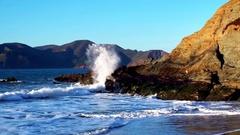 Golden Gate Bridge over waves crashing into beach mountainside 8 Stock Footage