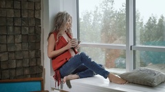 Young pregnant woman in red shirt sitting on the windowsill with the cup of tea Stock Footage