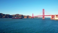 Container ship travels under Golden Gate Bridge by mountains Stock Footage