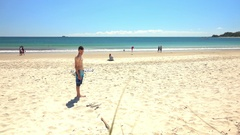 Australia, Byron Bay, Young Man Standing on the Beach, Looks At Camera Stock Footage