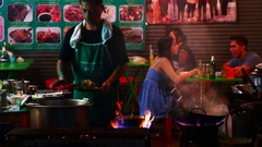 A chef cooks food at a street-side restaurant in Chinatown Stock Footage