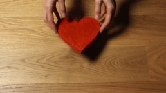 Beautiful female hands putting three red heart shapes on wooden table. Family Stock Footage