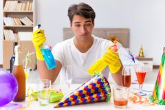 Man cleaning the house after party Stock Photos