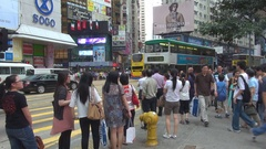 People crowd wait at traffic light tramway traffic in Hong Kong shopping area Stock Footage