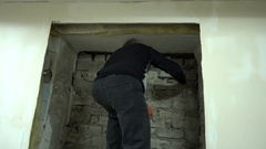 Man breaks parses Brick Wall with Chisel and Hammer Stock Footage