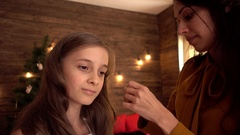 Mom puts Hairpin in Daughter's Hair - Christmas Eve near tree Stock Footage