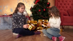 Girls sister dividing gifts under the tree - Christmas eve Stock Footage