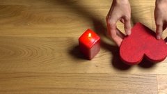 Woman hands putting two red heart shapes near candle. Love, romance, Valentine's Stock Footage