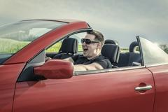 Angry man driving a car. Stock Photos