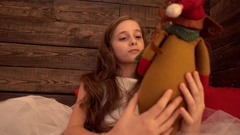 One sad Girl in Bed in white Dress with plush Christmas Deer Stock Footage