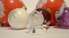 Christmas decorations. Snow falling in shiny magical crystal ball with snowman Stock Footage