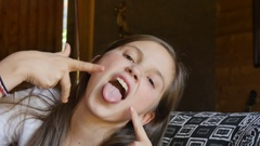 Beautiful young teen girl makes grimaces face Stock Footage